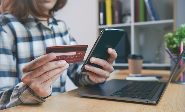 Mujer joven, tenencia, tarjeta de crédito, y, utilizar, teléfono inteligente, compra, onl