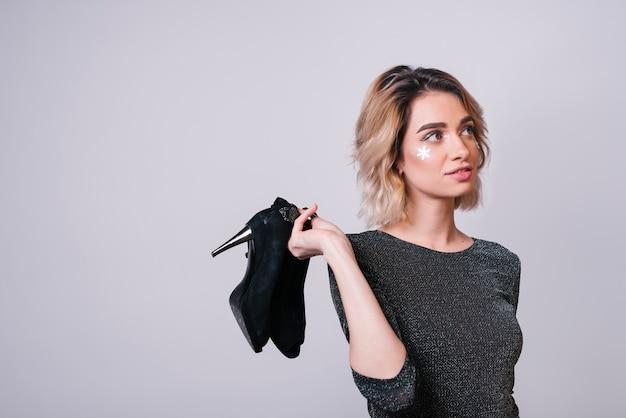 Mujer joven, tenencia, zapatos, después, fiesta