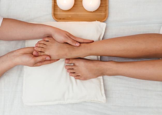 Mujer joven, tener, pies y piernas, masaje, en, salón de belleza, balneario, cicatrizarse