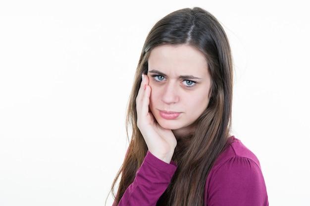 La mujer joven está teniendo un dolor de muelas.