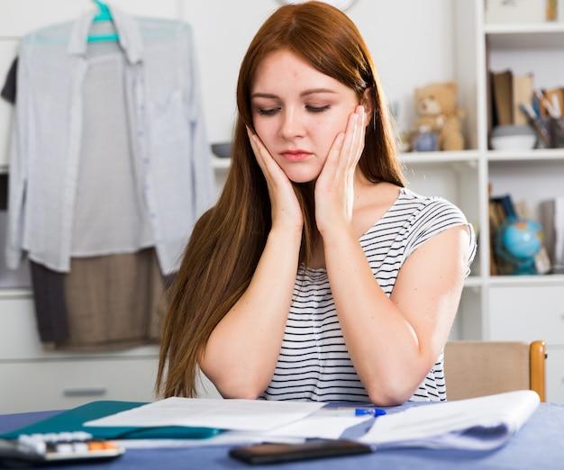 La mujer joven está teniendo problemas con el proyecto para el trabajo