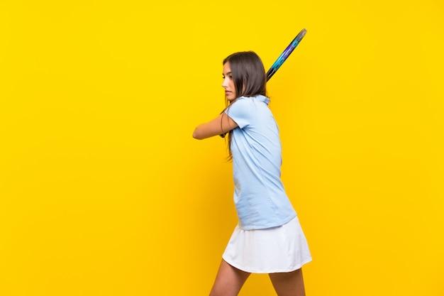 Mujer joven tenista sobre pared amarilla aislada