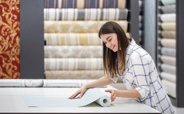 Una mujer joven en una tienda elige papel tapiz para su hogar. concepto de reparación y compras.