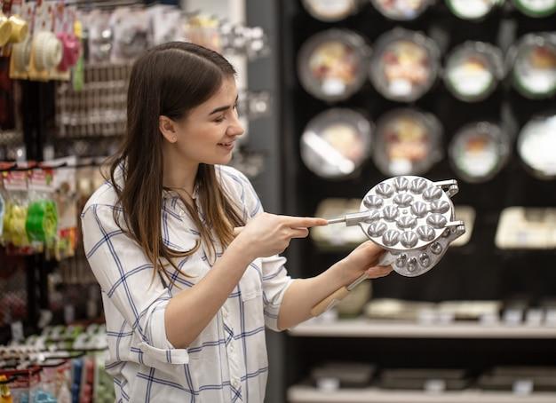 Mujer joven en la tienda elige una sartén