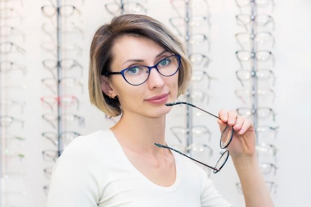 Mujer joven en tienda de óptica eligiendo gafas nuevas con óptico. gafas en la tienda de óptica. una mujer elige gafas. emociones oftalmología.
