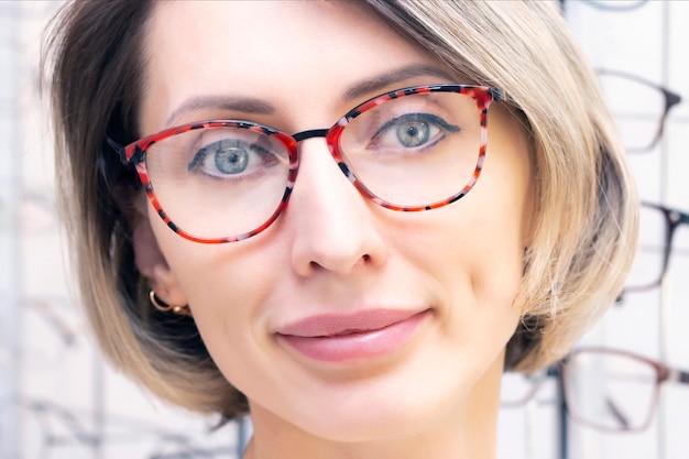 Mujer joven en tienda de óptica eligiendo gafas nuevas con óptico. gafas en la tienda de óptica