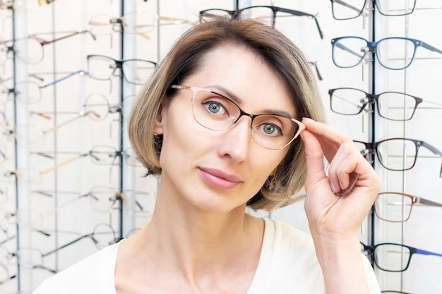 Mujer joven en tienda de óptica eligiendo gafas nuevas con óptico