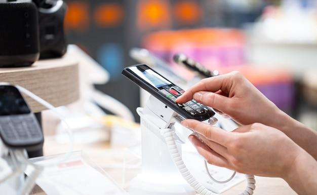 Una mujer joven en la tienda está de pie cerca del stand y elige un teléfono