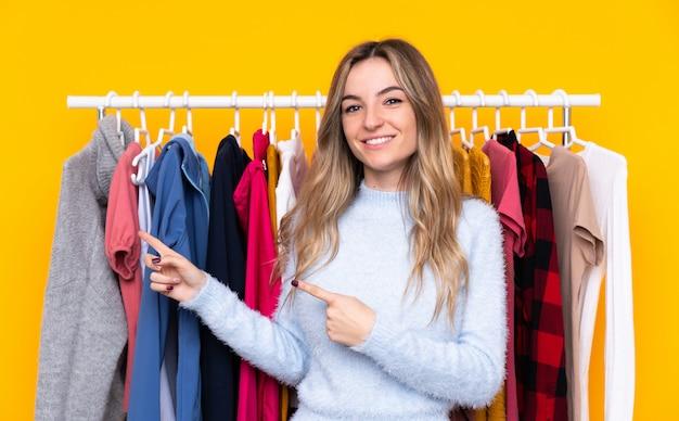 Mujer joven en una tienda de ropa apuntando con el dedo al lado