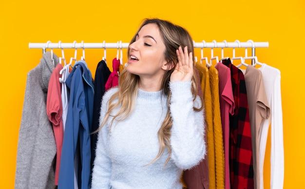 Mujer joven en una tienda de ropa sobre la pared amarilla aislada escuchando algo
