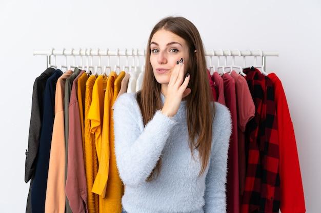Mujer joven en una tienda de ropa susurrando algo