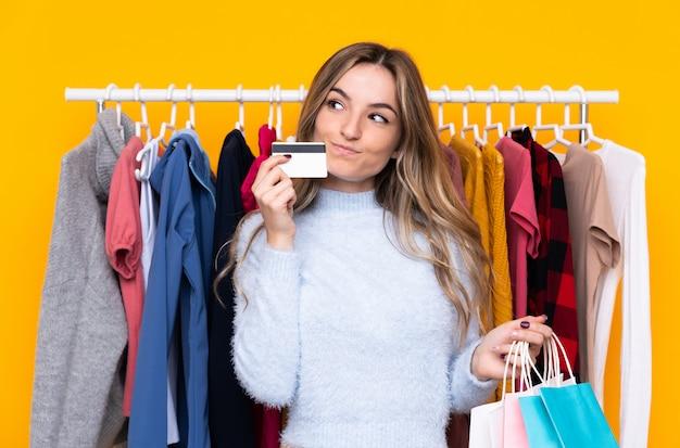 Mujer joven en una tienda de ropa con una tarjeta de crédito y con bolsas de compras