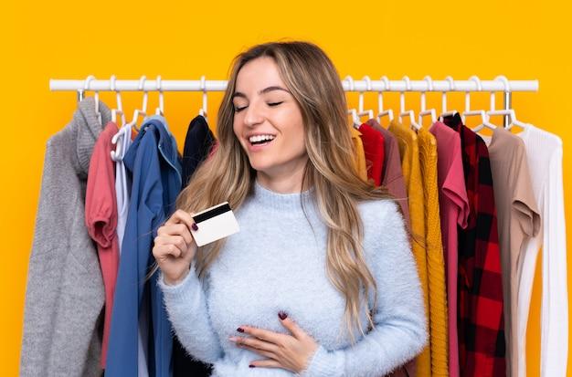 Mujer joven en una tienda de ropa con una tarjeta de crédito