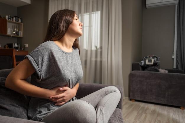 Mujer joven tiene dolor de estómago, enfermedad de la vesícula biliar