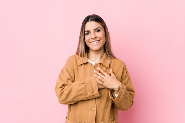La mujer joven tiene una expresión amigable, presionando la palma contra el pecho