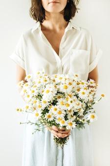 Mujer joven tiene en las manos ramo de flores de margarita blanca sobre superficie blanca