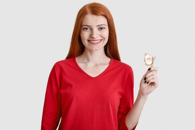 La mujer joven tiene el pelo largo, sostiene el condón, previene enfermedades de transmisión sexual