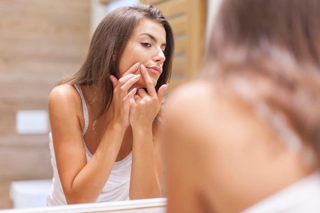 Mujer joven tiene problemas con la piel de la cara.