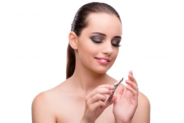 Mujer joven con unas tijeras para uñas aisladas en blanco