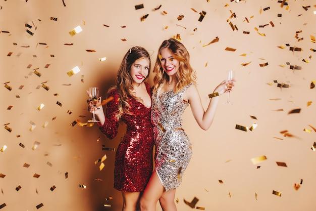 Mujer joven tímida en vestido rojo levantando una copa de champán con un amigo