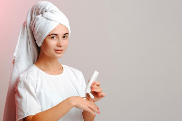 Mujer joven en una toalla de cabeza y camiseta blanca aplicando crema a mano del tubo. hacer la piel limpia, lisa e hidratada.