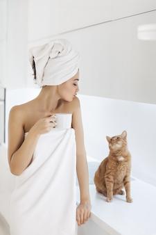 Mujer joven en toalla disfrutando de café en casa.