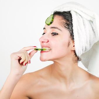 Mujer joven con la toalla envuelta alrededor de su cabeza que come la rebanada del pepino