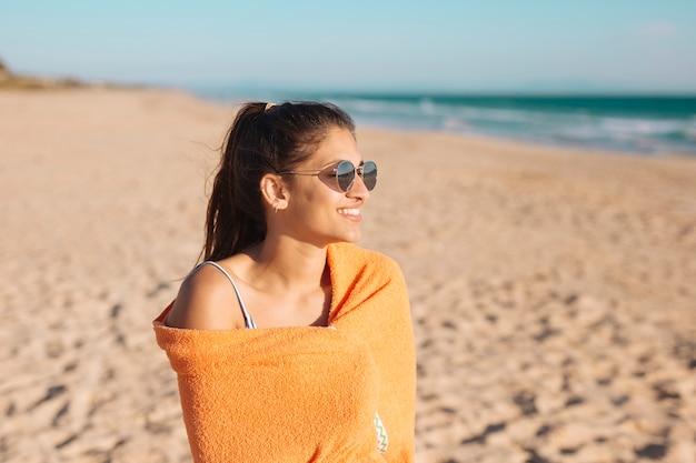 Mujer joven, con, toalla, en, playa arenosa