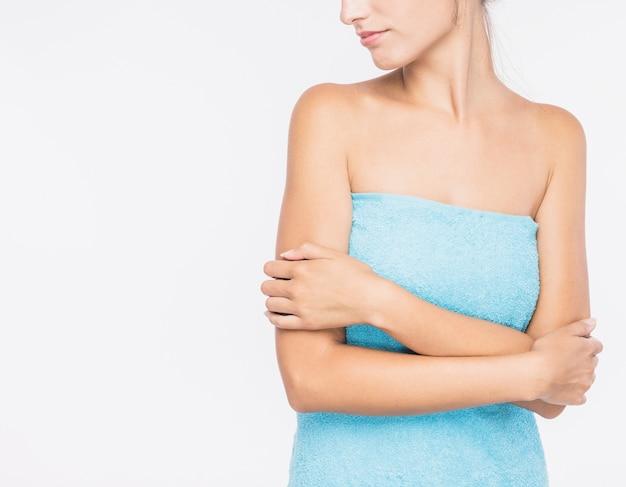 Mujer joven en toalla sobre fondo blanco