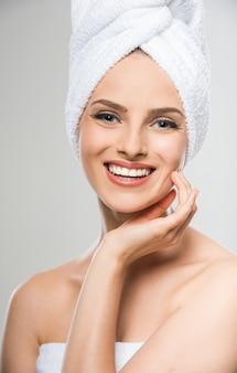 Mujer joven con una toalla en su cabeza después del baño.