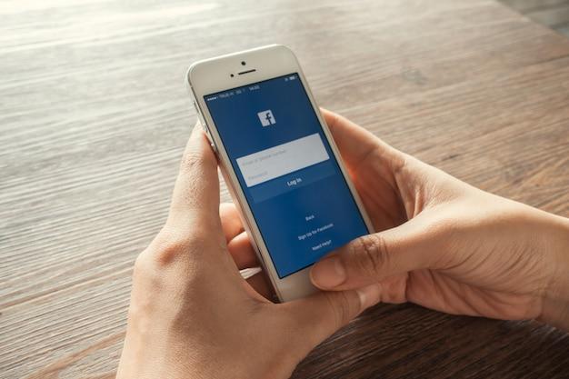 Mujer joven toca los iconos de facebook en el teléfono inteligente