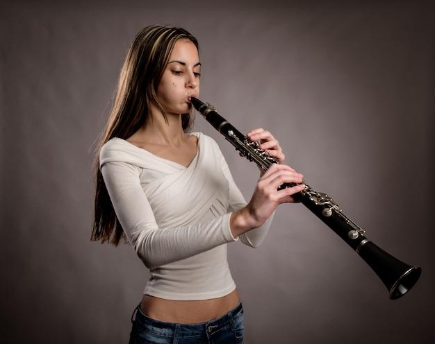 Mujer joven tocando un clarinete en un gris