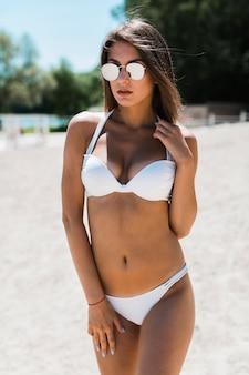 Mujer joven tocando la correa del sujetador de bikini
