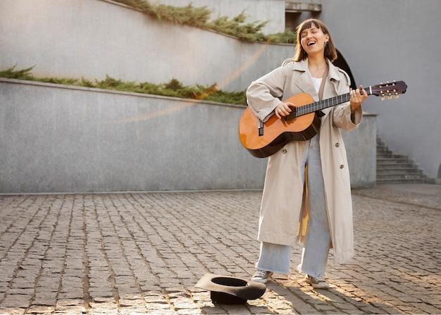 Mujer joven tocando la guitarra al aire libre con espacio de copia
