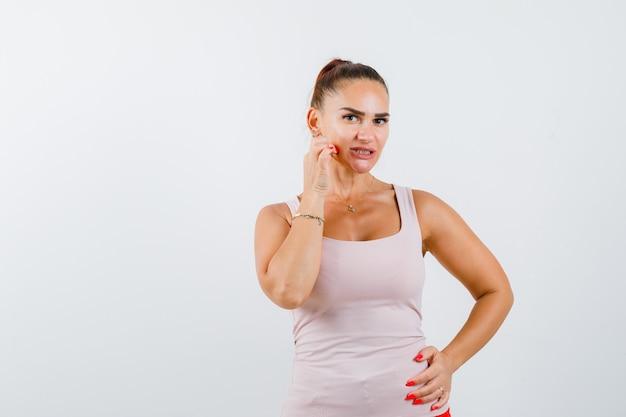 Mujer joven tocando la mejilla en camiseta y mirando confiado. vista frontal.
