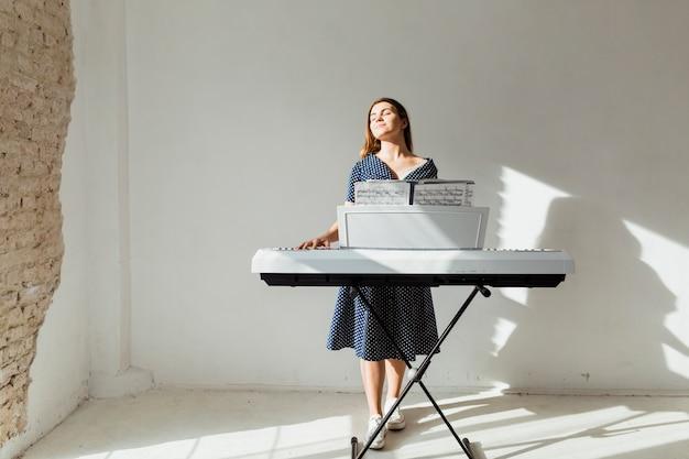 Mujer joven tocando el piano disfrutando de la luz del sol