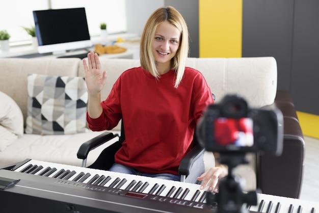 Mujer joven tocando el piano y saludando a la cámara en casa