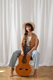 Mujer joven, tocar la guitarra, adentro