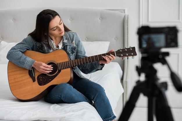 Mujer joven, tocar la guitarra