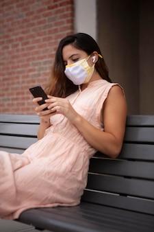 Mujer joven tolerando la ola de calor mientras usa una máscara médica