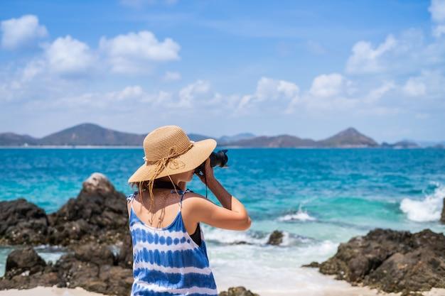 Mujer joven toma una foto en la playa tropical