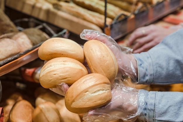 Una mujer joven toma del mostrador en el supermercado pan fresco.
