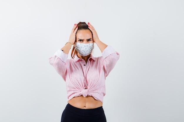 Mujer joven tomados de la mano en la cabeza en camisa, pantalón, máscara médica y mirando olvidadizo, vista frontal.