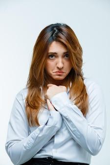 Mujer joven tomados de la mano en el pecho y mirando triste