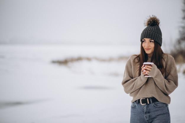 Mujer joven tomando café afuera en el parque de invierno