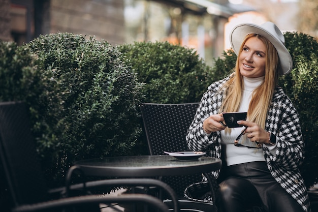 Mujer joven tomando café en un café