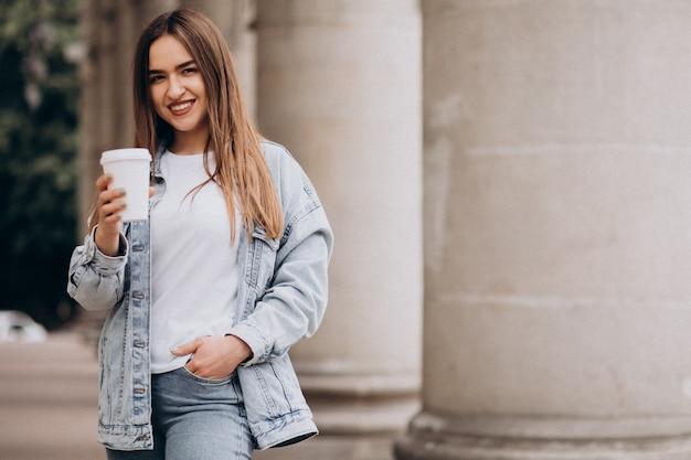 Mujer joven tomando café en la ciudad