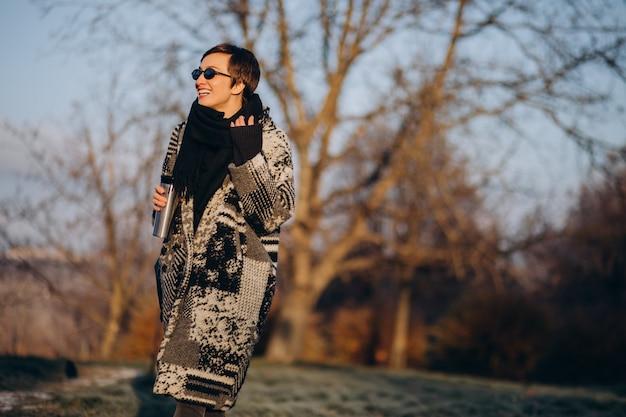 Mujer joven tomando café por la mañana y caminando en el parque