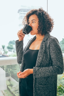 Mujer joven tomando café