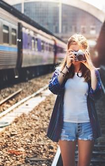 La mujer joven está tomando la foto con la cámara de la película